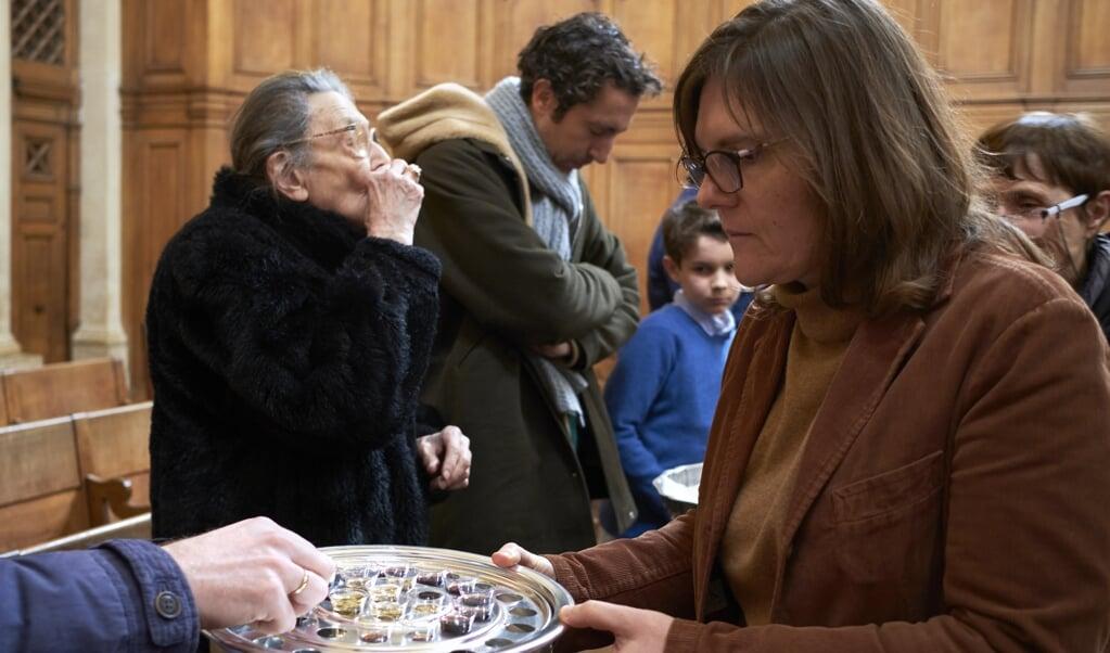<p>Een avondmaalsviering in een protestantse kerk in Parijs, kort voor de lockdown dit voorjaar als gevolg van de coronacrisis.</p>  (beeld Dick Vos)