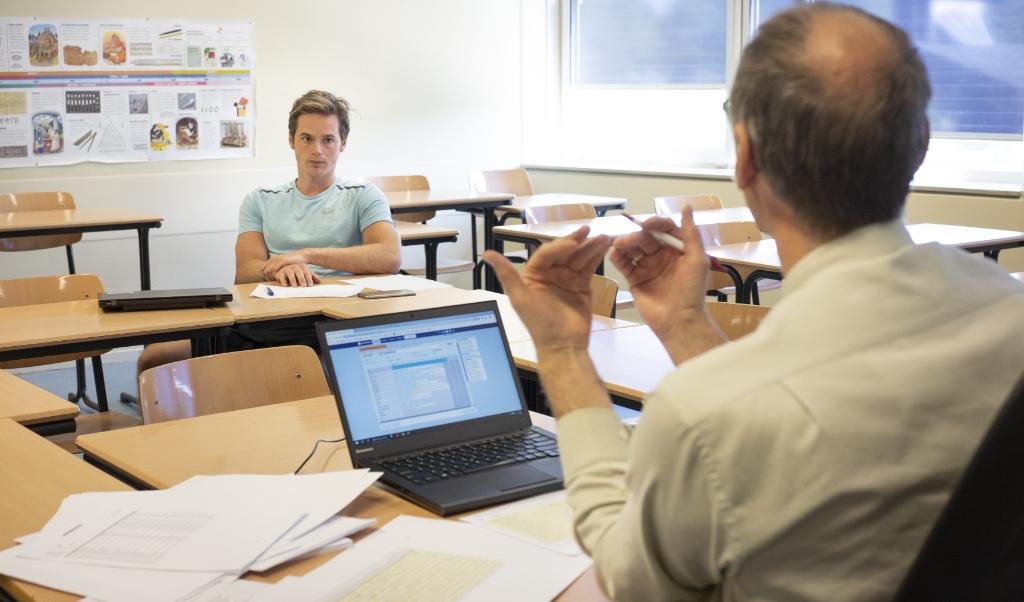 Harry van Dieren (op de voorgrond) overlegt met Jan Droogendijk, docent lichamelijke opvoeding en mentor van een havo-4-klas. 'De slow starters zijn de dupe van de coronacrisis.'  (beeld Niek Stam)