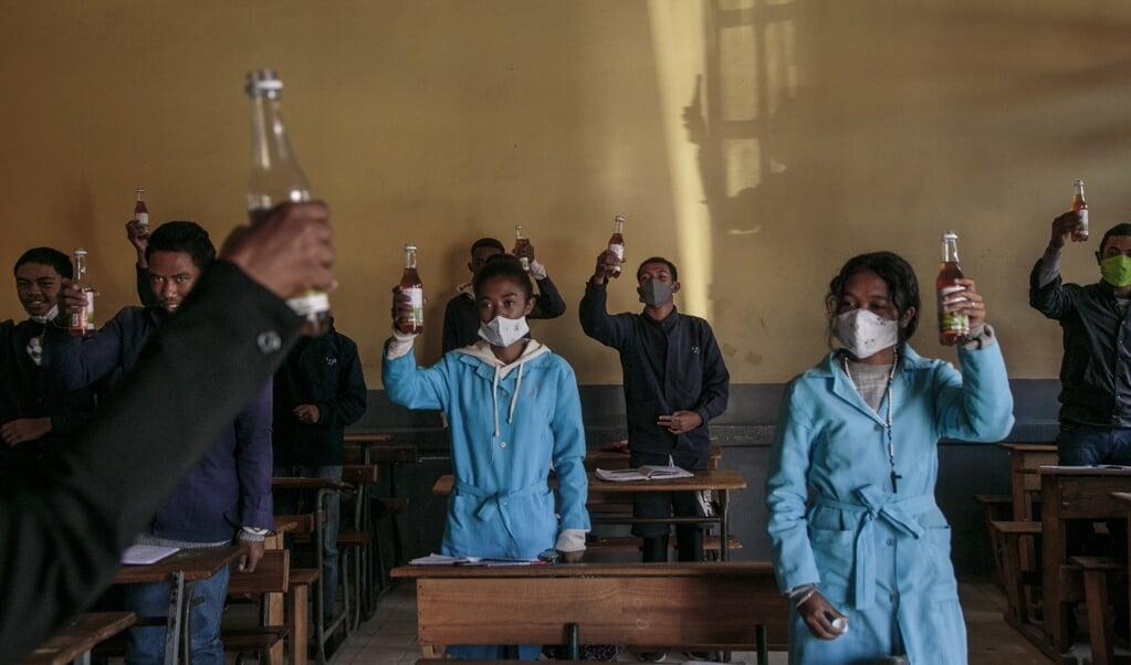 Scholieren in Madagaskar drinken het omstreden 'medicijn' Covid-Organics.  (beeld afp / Rijasolo)