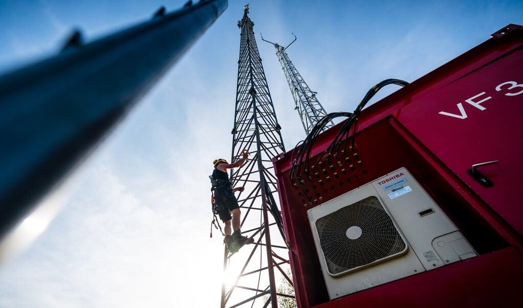 Een noodzendmast wordt opgebouwd nadat de vaste zendmast door brand vernield was. In de afgelopen maanden zijn meer zendmasten zwaar beschadigd door brand. De branden zijn vermoedelijk allemaal aangestoken  Vooral de komst van een 5G-netwerk voedt angst en wantrouwen.  (beeld anp / rob Engelaar)