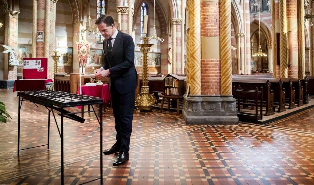 Premier Mark Rutte brandt een kaars in de St. Jacobskerk in Den Haag. Rutte besprak met een a afvaardiging van de Haagse Gemeenschap van Kerken hoe men in de kerk omgaat met vraagstukken rond het coronavirus.  (beeld anp / Remko de Waal)