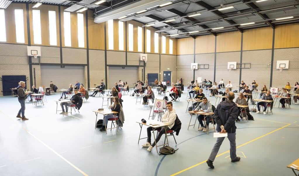 In de grote gymzaal zwoegen in normale tijden 210 leerlingen op hun examen. Nu buigen zestig havo-leerlingen zich over de wiskunde A-toets.  (beeld Niek Stam )