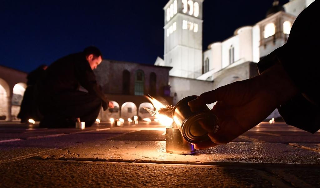 Ook de franciscanen pasten zich aan de lockdown aan. In Assisi, de stad van Franciscus en Clara staken de broeders op Goede Vrijdag kaarsen aan, in de vorm van een kruis.  (beeld afp / Tiziana Fabi)