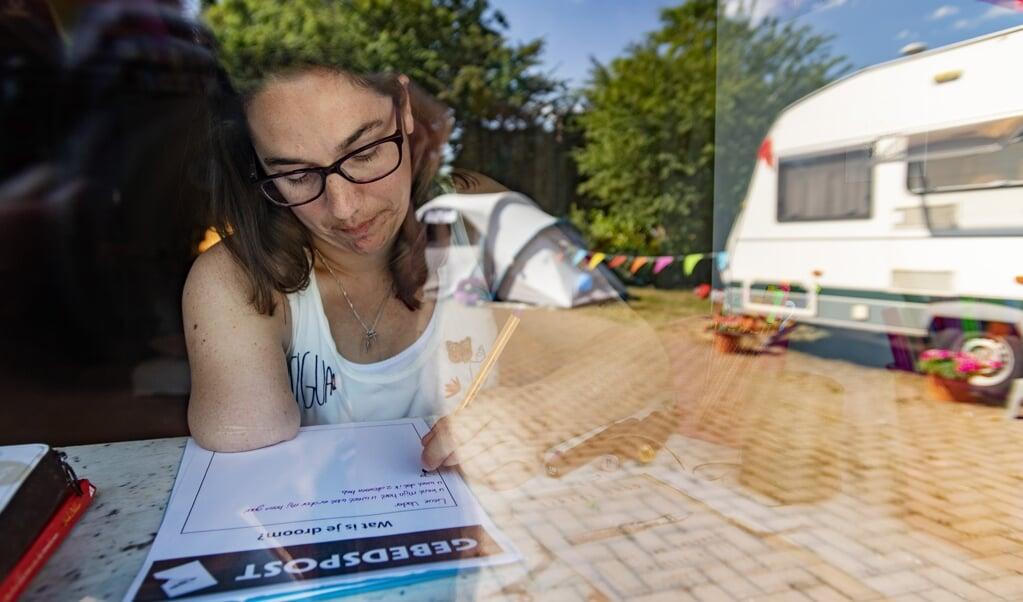 Peggy van Beek schrijft 'gebedspost' tijdens haar eigen georganiseerde Pinksterweekend.  (beeld beeld werkt / Jeroen van Eijndhoven)