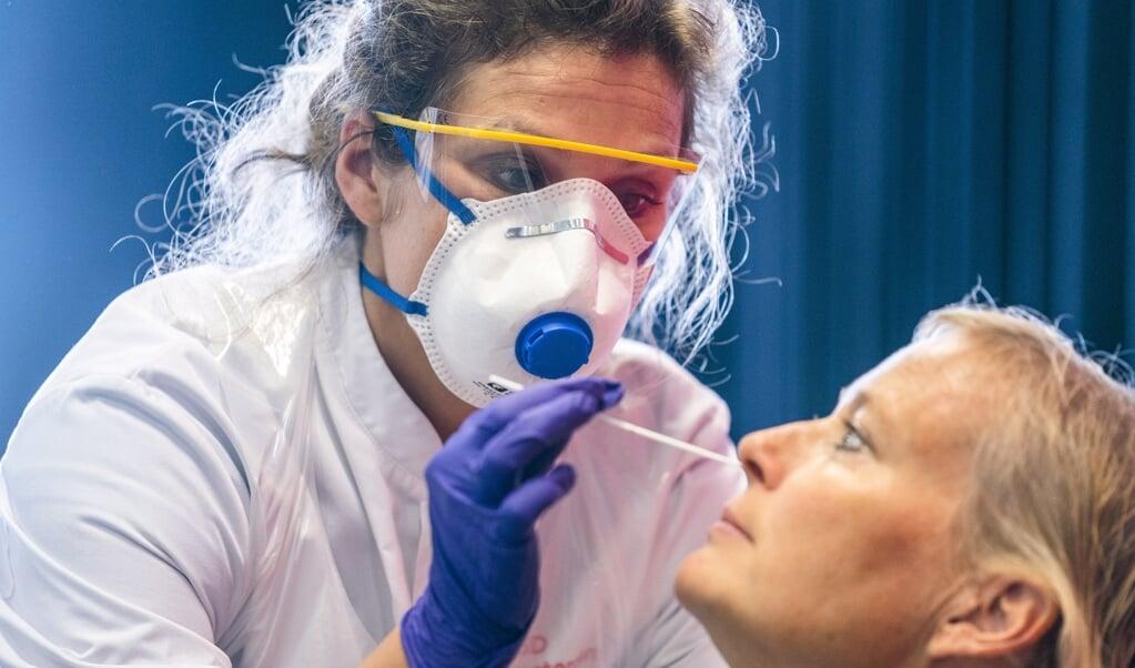 Een zorgmedewerker wordt getest op het coronavirus door medewerkers van de GGD Amsterdam.  (beeld anp / Jeroen Jumelet)