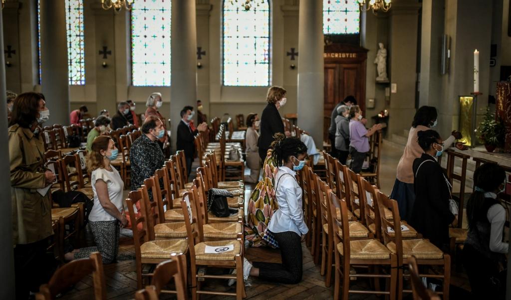 In de Saint Jean-Baptiste-kerk in een buitenwijk van Parijs komen mensen voor het eerst weer samen voor de mis. Frankrijk heeft het samenkomen in godsgebouwen na weken van beperkingen weer toegestaan.   (beeld AFP)