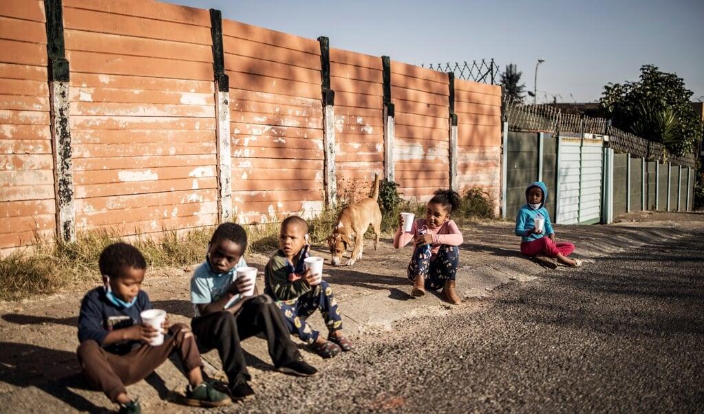 Kinderen in Zuid-Afrika met het ontbijt dat is verstrekt door een non-profitorganisatie.  (beeld afp / Marco Longari)