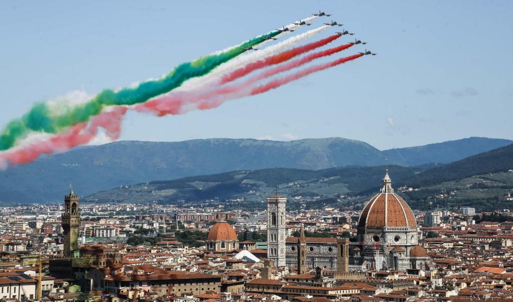 Negen vliegtuigen van het demonstratieteam van de Italiaanse luchtmacht, Frecce Tricolori, vlogen dinsdag over Florence. Rook in de nationale kleuren rood, wit en groen achter zich aan.  (beeld sipa / Claudio Fusi )