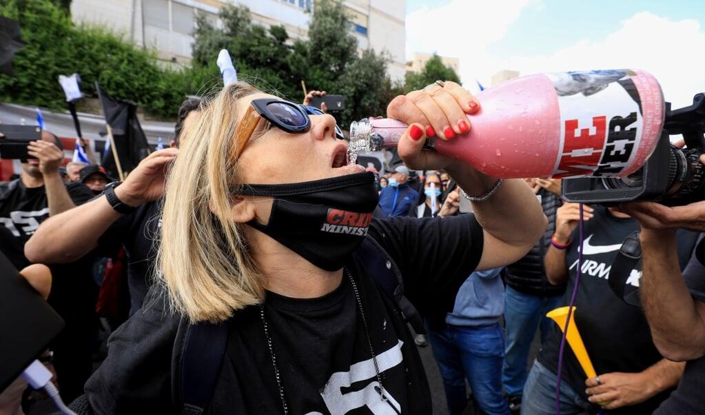 Tegenstanders van premier Netanyahu demonstreren bij zijn ambtswoning op de dag dat het proces tegen hem aanvangt.    (beeld afp )