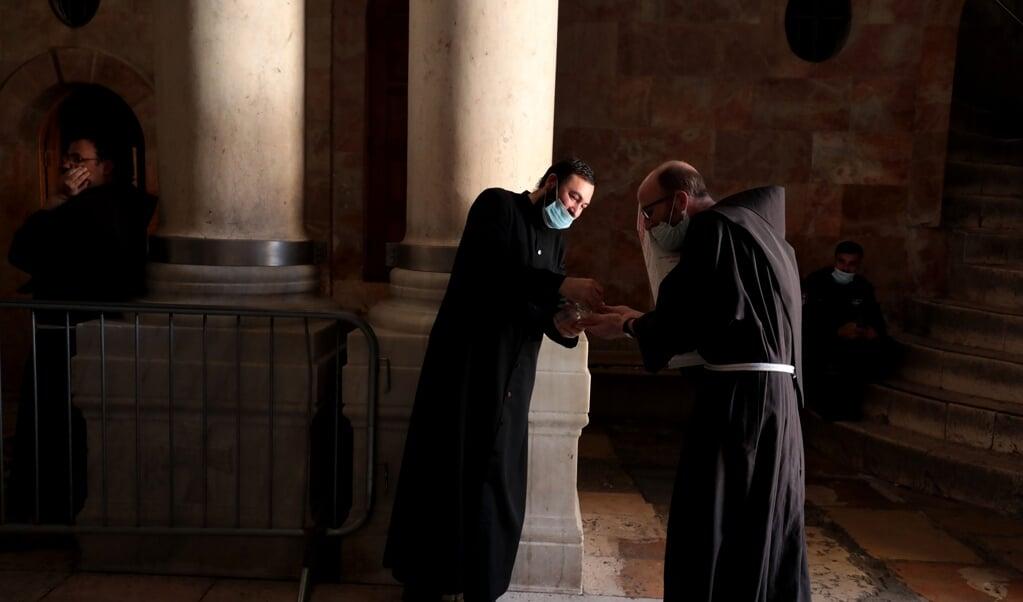 Een Armeense monnik geeft ontsmettende handgel aan een bezoeker van de Heilige Grafkerk in Jeruzalem.  (beeld afp / Gali Tibbon)