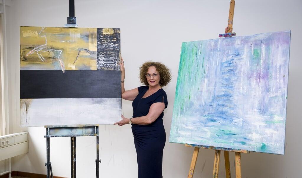 Juanita van der Groep in haar atelier, met haar werk over het witte en zwarte paard.  (beeld Richard van Hoek)