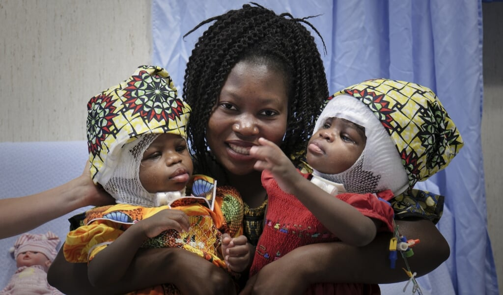 De tweeling Ervina en Prefina met hun moeder nadat hun achterhoofden en bloedvatensystemen in het Vaticaanse kinderziekenhuis Bambino Gesù van elkaar gescheiden waren.  (beeld afp / bambino gesu hospital)