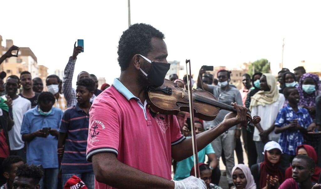 Tijdens een protest ter herdenking van de staatsgreep die dictator Omar al-Bashir 31 jaar geleden aan de macht bracht, speelde een Soedanees afgelopen 30 juni protestliederen op zijn viool. De demonstranten vroegen de overgangsregering om hervormingen.  (beeld epa / Mohamed Hassan)