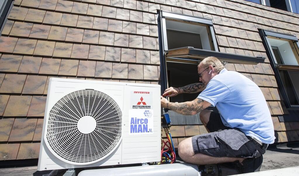 Een installateur plaats een airconditioner in een woning in Hooglanderveen. Door het warme weer gaan mensen op zoek naar verkoeling in hun huis.  (beeld anp / Pieter Stam de Jonge)