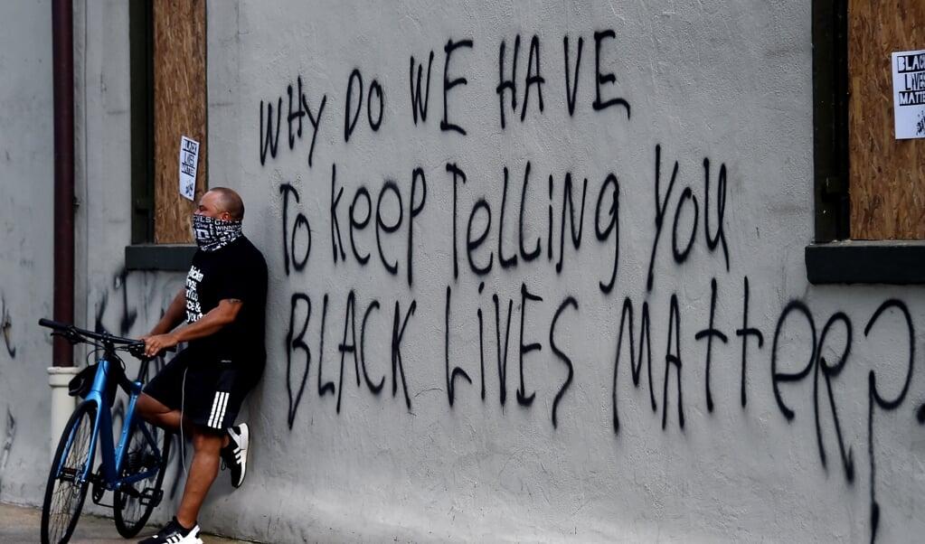 Op een muur in de buurt van het Witte Huis in Washington is een tekst gespoten die veel Amerikanen uit het hart is gegrepen: 'Waarom moeten we je blijven vertellen dat ook zwarte mensen ertoe doen?'  (beeld afp / Olivier Douliery)