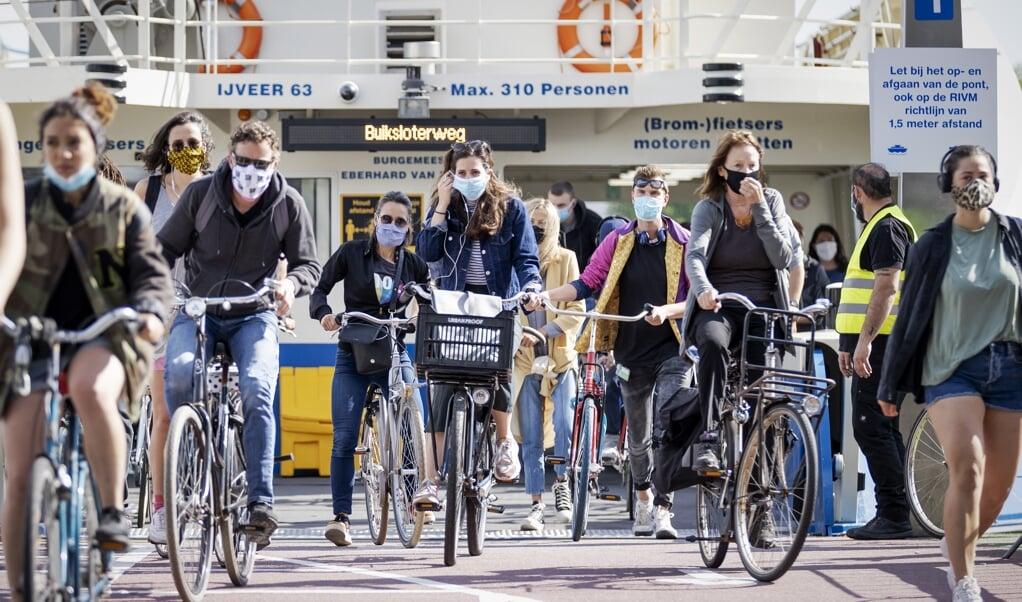Reizigers met mondkapjes bij de pont achter Amsterdam CS.   (beeld anp / Robin van Lonkhuijsen)