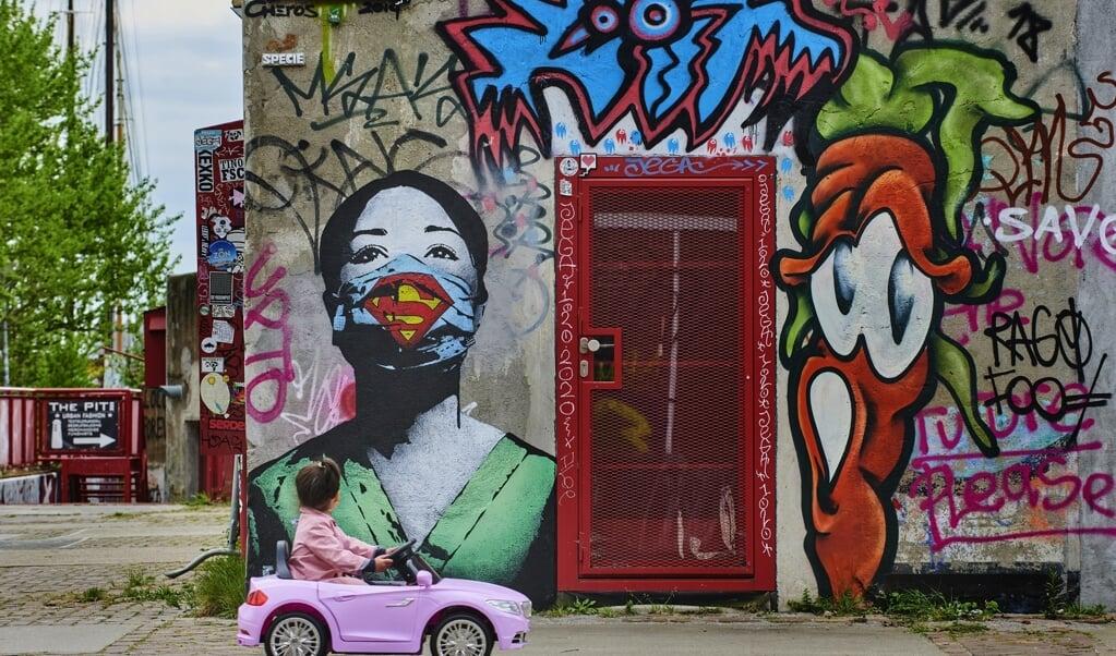 Een meisje kijkt naar graffitikunst van een superverpleegster op het NDSM-plein in Amsterdam.  (beeld Nico Garstman)