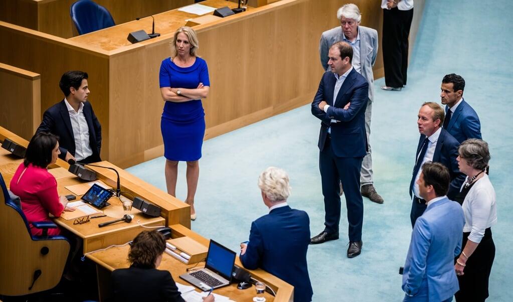 Kamerleden overleggen met Kamervoorzitter Khadija Arib tijdens een debat in de Tweede Kamer over het coronabeleid.  (beeld anp / Bart Maat)