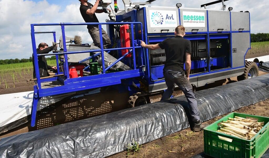 Een aspergeteler automatiseert en schaft een aspergesteekmachine aan. Technici installeren de machine.  (beeld Marcel van den Bergh)