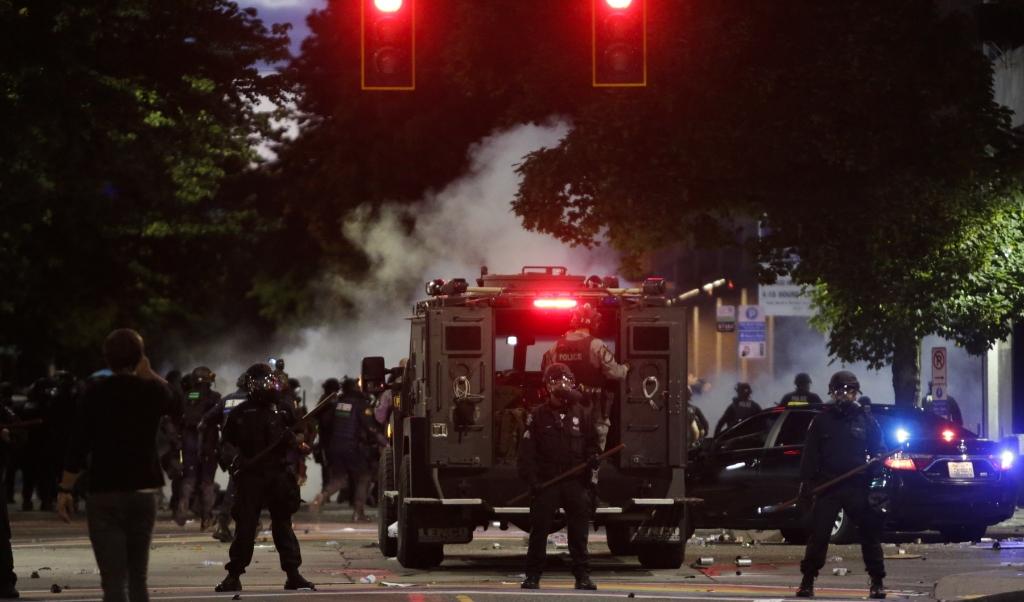 Zwaar bewapende politie in Seattle houdt de situatie in de gaten na het uiteendrijven van een demonstratie tegen het politiegeweld.  (beeld afp / Jason Redmond)