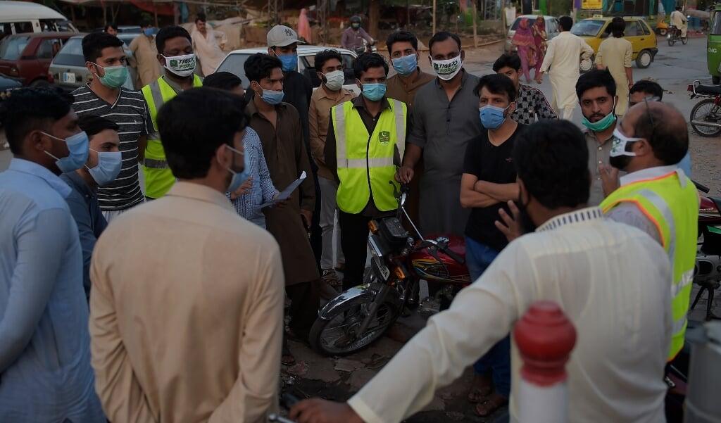 De Pakistaanse premier Imran Khan stuurt vrijwilligersteams het land in om mensen bewust te maken van corona. Volgens CGK Diaconie concentreert de hulp van de Pakistaanse overheid zich vooral op moslims.  (beeld AFP)