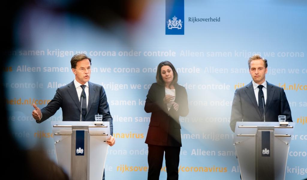 Premier Mark Rutte, coronaminister Hugo de Jonge en gebarentolk Irma Sluis tijdens de persconferentie over de coronacrisis.  (beeld anp / Bart Maat)