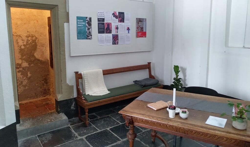 In de kerkkluis staan een kerkbank met dekentjes, een oude tafel en een moderne stoel.  (beeld nd)