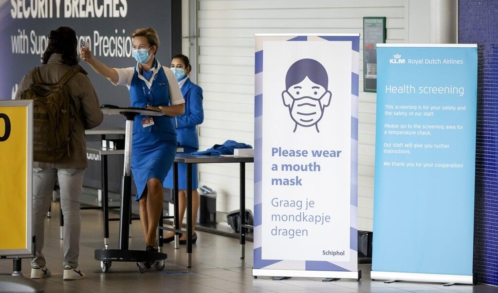 KLM-stewardessen controleren op Schiphol de temperatuur van passagiers.  (beeld anp / Robin van Lonkhuijsen)