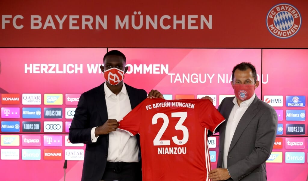 Hasan Salihamidzic (r.), technisch directeur van Bayern München, presenteert aankoop Tanguy Nianzou. Ondanks de coronacrisis gingen clubs gewoon door met spelers kopen voor forse bedragen.  (beeld epa / Alexander Hassenstein)