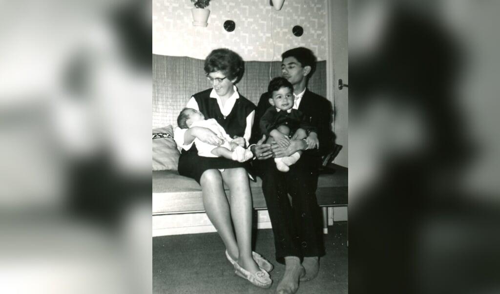 Ronald Hünnenman, hier bij zijn vader opschoot: 'Mijn ouders, mijn jongere broer en ik' (1963). 'Als mijn lichtere broer en ik samen met mijn moeder over straat liepen, riep ze wel eens lachend naar een buurvrouw: 'Ja hoor, deze is van de melkboer'.  (beeld nd)
