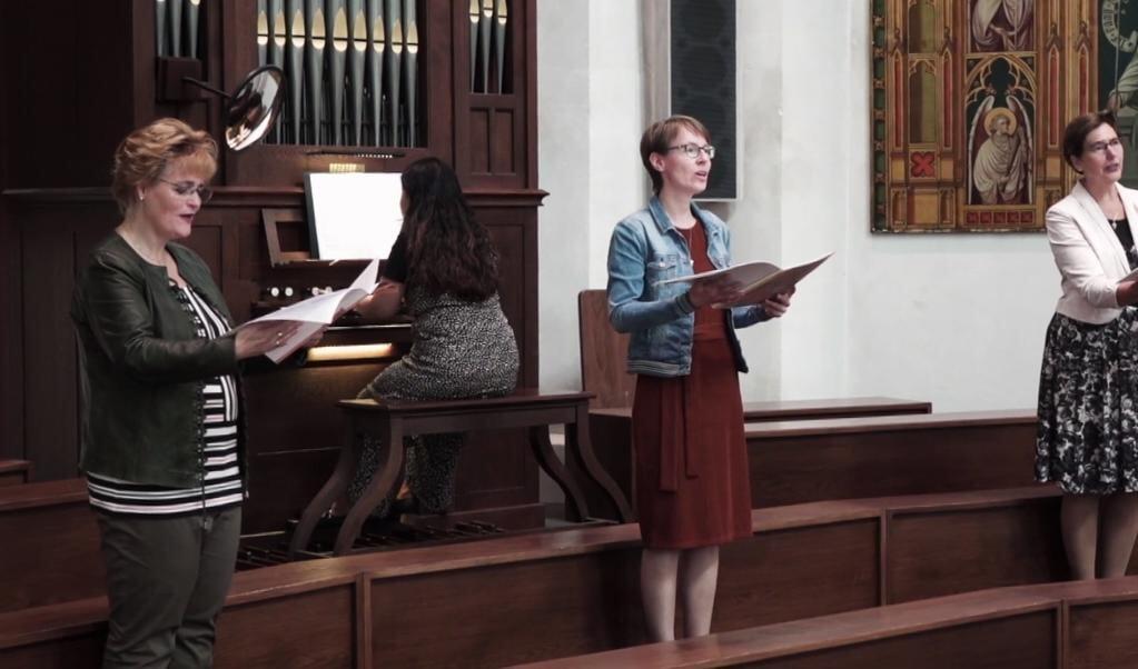 Karin Timmer, Rosali Viveen en Sonja Roskamp zingen het 'Lam Gods' uit de Missa Corona, op orgel begeleid door Cecilia Raymakers.  (beeld vimeo)