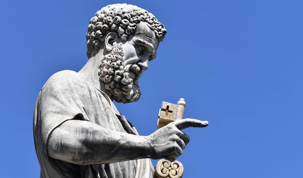 Het beeld van de apostel Petrus op het Sint-Pietersplein in Rome. Hij kijkt met de 'sleutel van het koninkrijk der hemelen' in de hand uit over de stad Rome en de wereld.   (beeld afp / Andreas Solaro)