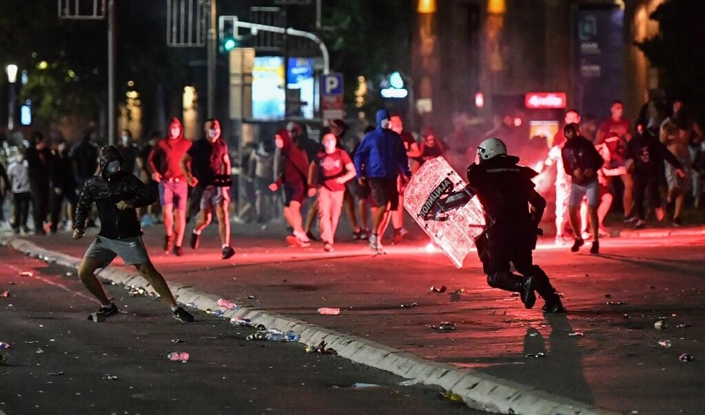 Servische politieagenten grijpen in tijdens een demonstratie, vorige week, in de Servische hoofdstad Belgrado.  (beeld afp / Andrej Isakovic)
