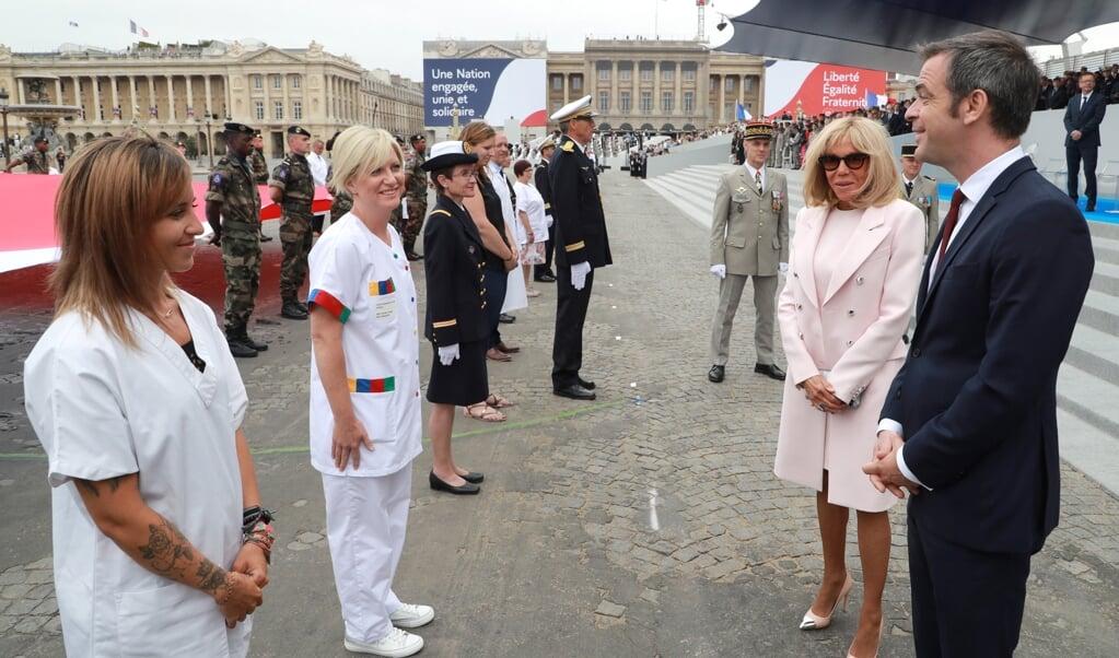 De Franse minister van Gezondheidszorg Olivier Véran (rechts) en first lady Brigitte Macron spreken met zorgpersoneel.   (beeld epa / Ludovic Marin)