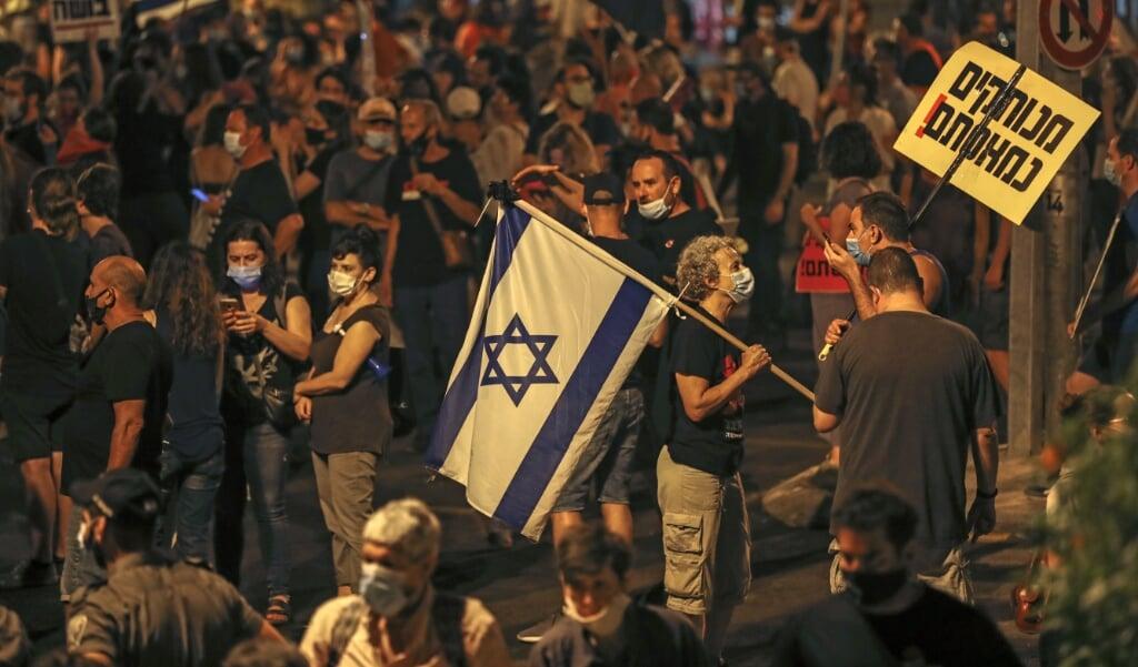 Duizenden Israëliërs protesteren iedere dag tegen premier Benjamin Netanyahu. Een 'groot thema' ontbreekt echter, zegt onderzoeker Padan.  (beeld afp / Ahmad Gharabli)