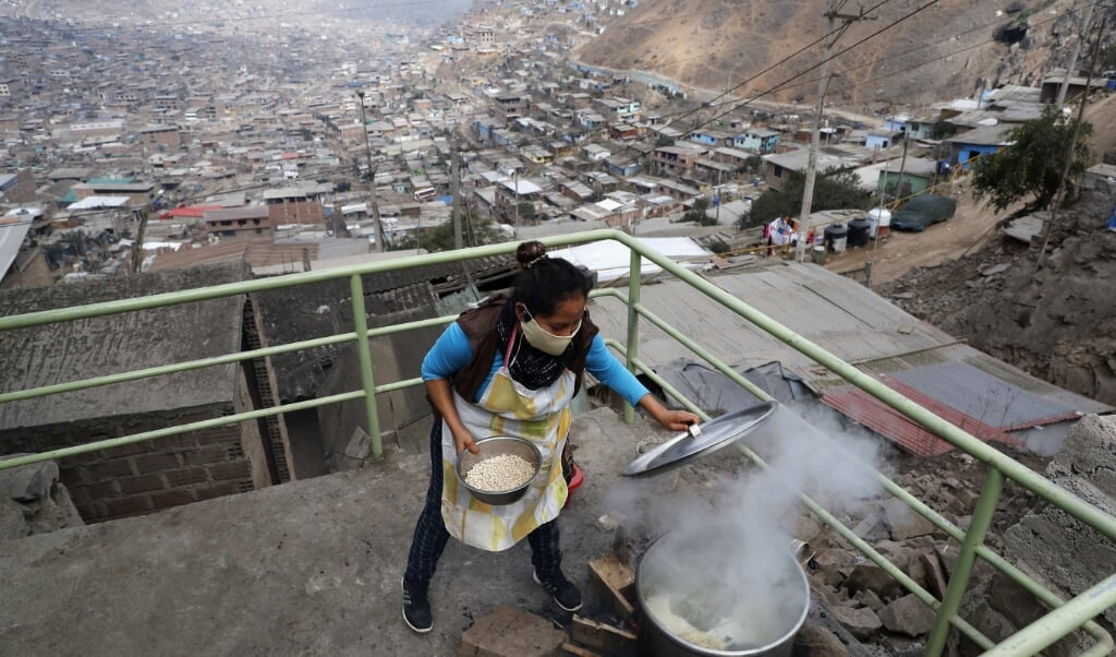 Een vrouw in Lima, Peru bereidt een maaltijd. 'Je kunt sterven aan COVID-19, maar niet aan honger', luidt het motto van Jose Luis Calvo, een Spaanse parochiepriester die in Peru een groot netwerk van donaties heeft opgezet om elke dag een maaltijd voor achtduizend kansarme mensen te verzorgen in een van de armste uithoeken van Lima.   (beeld epa / Paolo Aguilar)
