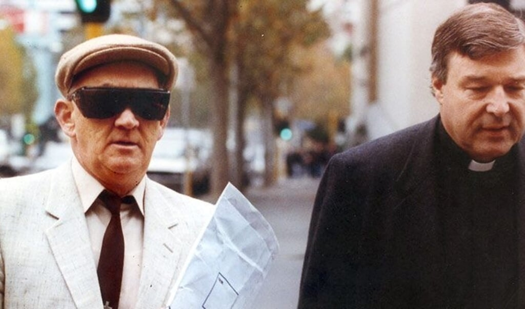 De latere kardinaal George Pell (rechts) begeleidt zijn voormalige collega en mede-priester Gerald Lindsdale, in 1993 naar de rechtbank voor diens misbruikproces.  (beeld afp)