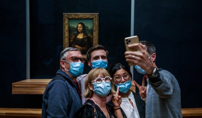 Bezoekers met mondmaskers op poseren bij de Mona Lisa. Het Louvre opende maandag na vier maanden weer zijn deuren.  (beeld epa / Christophe Petit Tesson)