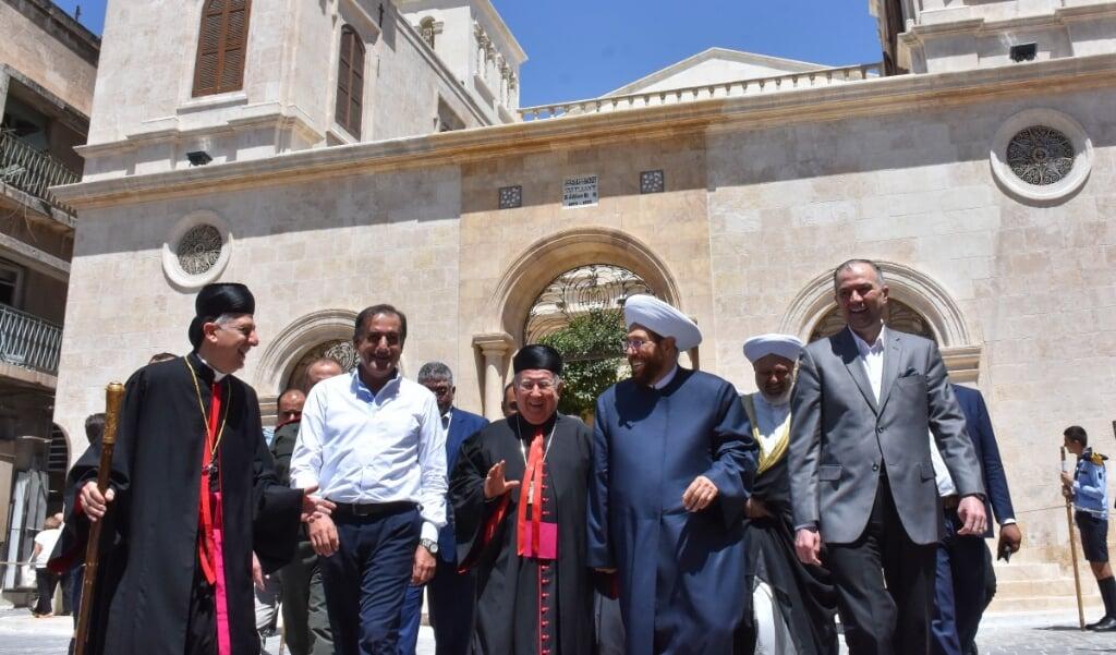 Aartsbisschop Joseph Tobji van Aleppo (links) met aartsbisschop Paul Youssef Matar uit Beiroet (midden), en de grootmoefti van Syrië Ahmed Hassoun (tweede van rechts) vlak na de heropening van de maronitische kathedraal in Aleppo.  (beeld afp)