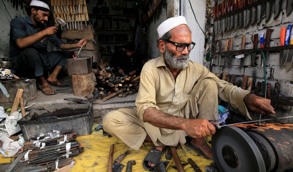 Een smid scherpt messen die gebruikt worden voor het slachten van offerdieren. In Pakistan worden offerdieren geregeld thuis geslacht.  (beeld epa/ Bilawal Arbab)