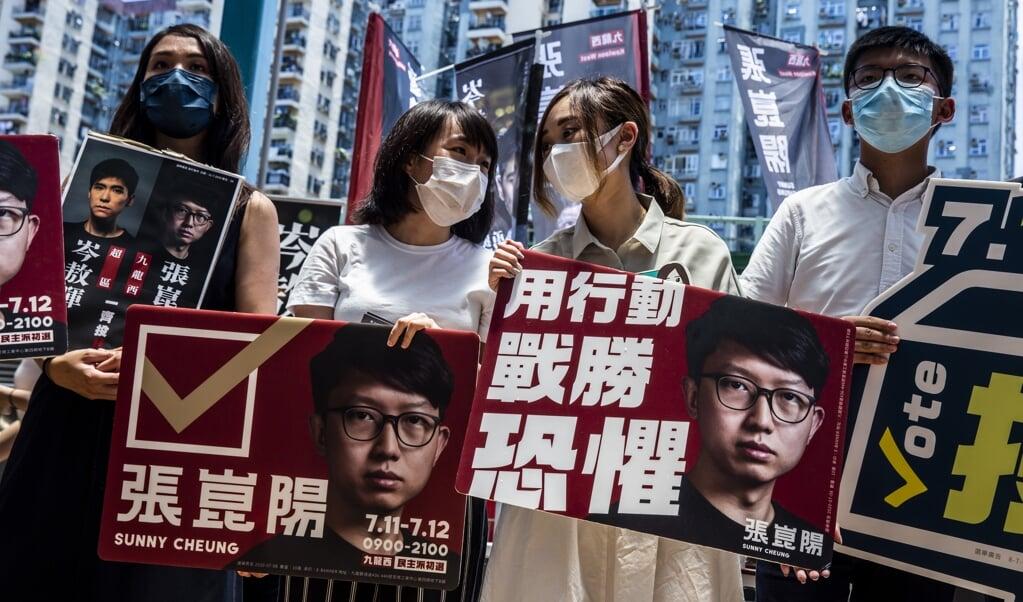 De activisten Gwyneth Ho, Leung Hoi-ching, Tiffany Yuen en Joshua Wong tijdens de voorverkiezingen van dit weekend.  (beeld afp / Isaac Lawrence)