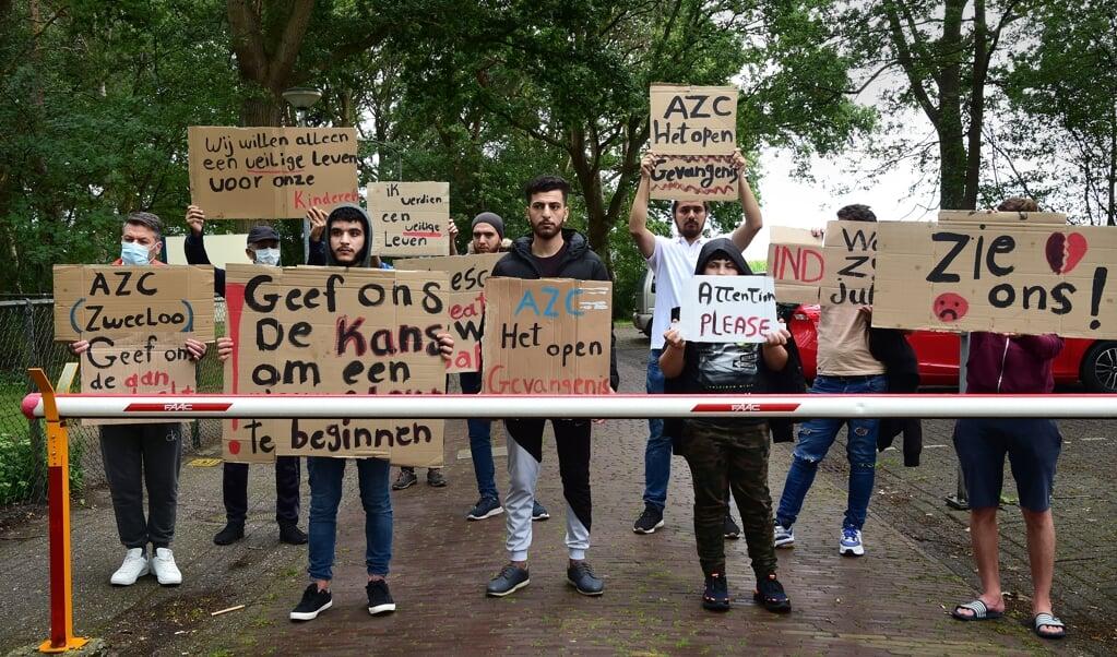 Voor de poort van het asielzoekerscentrum in Zweeloo protesteren asielzoekers, eind juli, tegen de ongelijke behandeling van asielaanvragen.  (beeld Marcel van den Bergh)