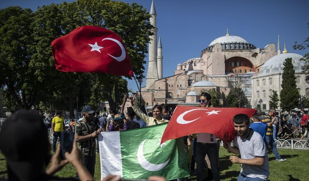 Mensen poseren met Turkse en Pakistaanse vlaggen bij de Hagia Sophia uit vreugde dat deze weer een moskee is geworden.  (beeld Epa/Erdem Sahin)