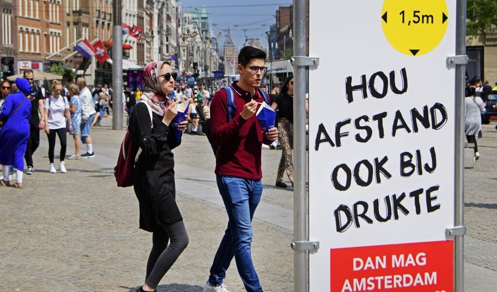 Een informatiebord in het centrum. De Veiligheidsregio Amsterdam-Amstelland neemt extra maatregelen vanwege de toenemende drukte in de binnenstad.  (beeld anp / Olaf Kraak)