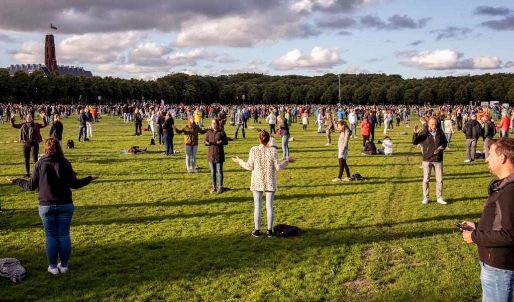 Zo'n tweeduizend mensen baden en zongen vrijdagavond op het Malieveld in Den Haag.   (beeld Dirk Hol )