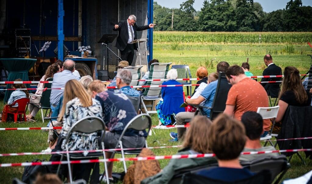 Kerkgangers tijdens een kerkdienst op een weiland in Barneveld.  (beeld anp / rob Engelaar)