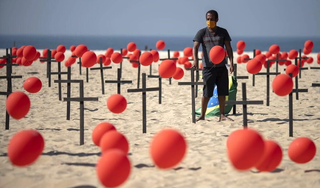 Brazilianen op het strand van Rio de Janeiro brengen met kruizen en ballonnen een eerbetoon aan meer dan honderdduizend coronadoden.  (beeld afp / Mauro Pimentel)