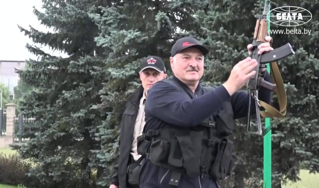 Het staatspersbureau Belta toonde zondag opnamen waarin de president van Belarus Aleksandr Loekasjenko te zien is met machinegeweer en scherfvest.  (beeld afp / belta)