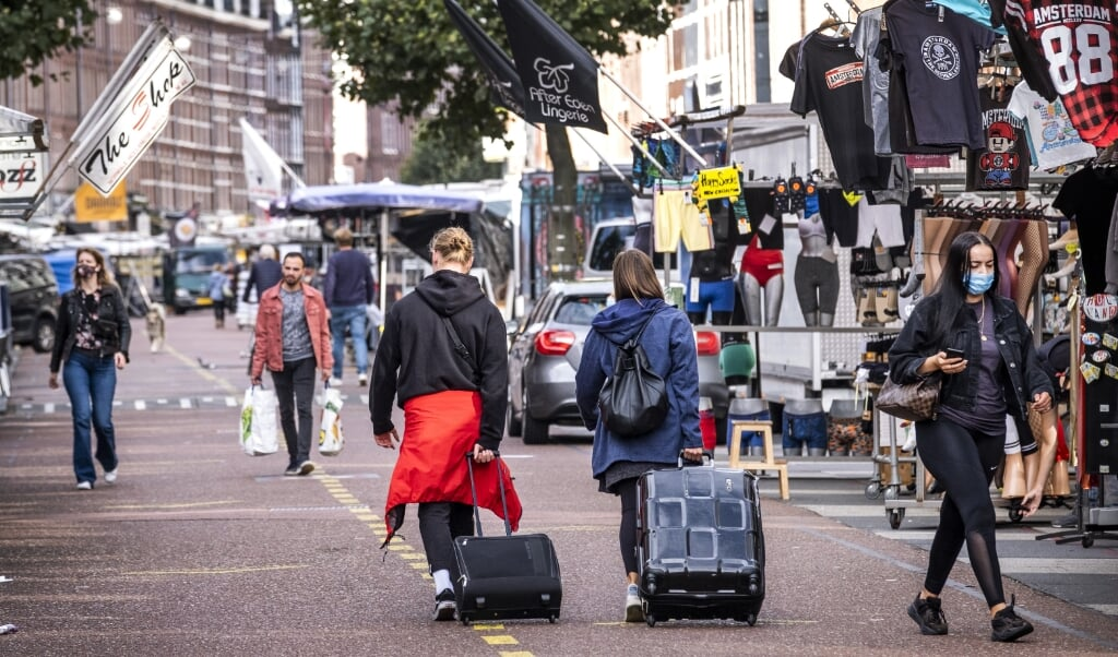 <p>Toeristen op de Amsterdamse Albert Cuypmarkt. In Amsterdam heeft Airbnb niet bij iedereen een goede naam, omdat de Amerikanen worden gezien als ontwrichters van de woningmarkt.</p>  (beeld anp / Ramon van Flymen)