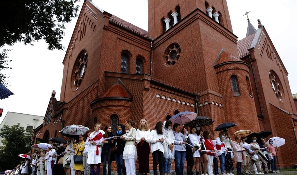 <p>Vrouwen demonstreren bij de &#39;rode&#39; Simon en Helena, een rooms-katholieke kerk in Minsk, Belarus.</p>  (beeld Epa/tatyana Zenkovich)